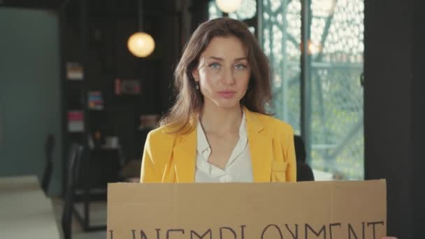 NEW YORK - March, 28, 2020: Dismissed young serious woman holding Unemployment carton banner strike at office workspace while leaving corporate company. Job loss. Financial crisis 2020.