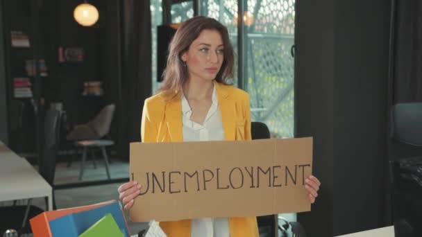 Young upset woman dismissed from job holding an important sigh banner saying Unemployment leaving the company. Global job losses. Financial crisis 2020.