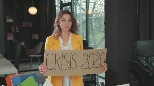 NEW YORK - March, 28, 2020: Portrait of dismissed young woman showing a Crisis 2020 banner sign after she got job dismissal standing in corporate office room. Unemployment.