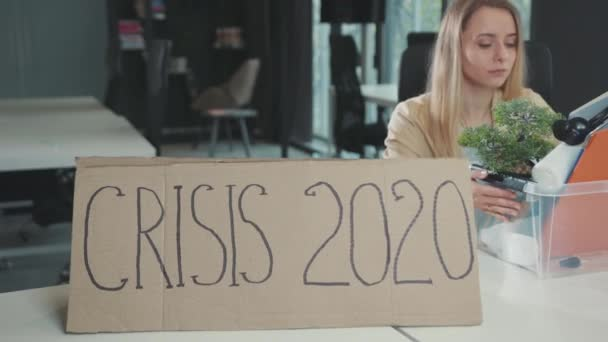 Fired young woman quitting job and leaving the office with personal items box. Crisis 2020 banner on working table. Global unemployment. Lockdown. Quarantine.