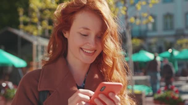 Beautiful young red-haired caucasian woman girl student using smartphone social media app messaging smile satisfied stay outside on sunny spring day. Urban people lifestyle.