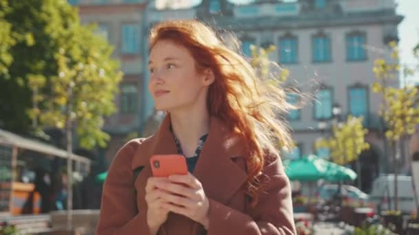 Appealing cute dreamy young woman with curly red hair using smartphone messaging with boyfriend smile satisfied enjoying walk in beautiful downtown outdoors.