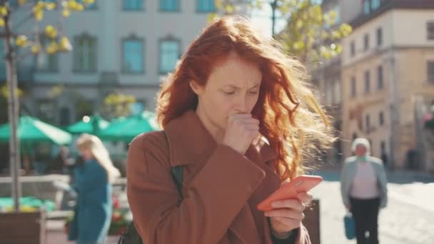 Young poor unhealthy woman with curly ginger hair holding smartphone coughing into fist feels badly suffering virus symptoms. Coronavirus. Pandemic. Sickness, infection concept.