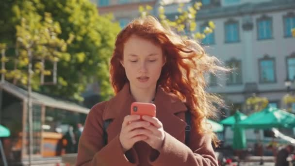 Ginger young female student using smartphone app messaging in city center. Poor unhealthy red-haired woman feeling bad headache pain touching temples. Healthcare. Pandemic.
