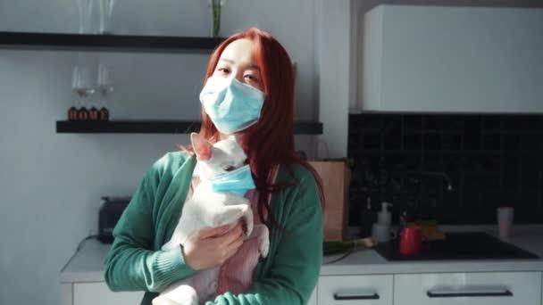 Hezká mladá asijská žena drží bílé roztomilé čivavy štěně v rukou, objímání a nošení lékařských masek v kuchyni. Zůstaň doma. Koronavirus. Koncept zdravotní péče.