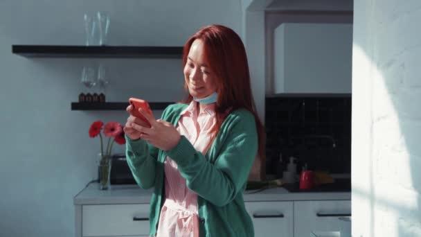 Fröhliche junge rothaarige Chinesin in lässiger Kleidung, die in den sozialen Medien Smartphone-Netzwerke nutzt und in der Küche steht. Soziale Distanz. Zu Hause bleiben.