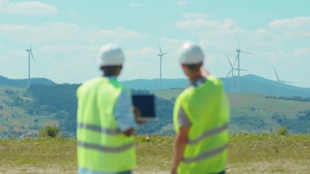 Schuss zurück zwei Ingenieure verwenden Laptop-Ständer in der Nähe von Windmühlen in Feldern Teamarbeit Zusammenarbeit Beitrag Windkraftpark Techniker sprechen Nahaufnahme Zeitlupe
