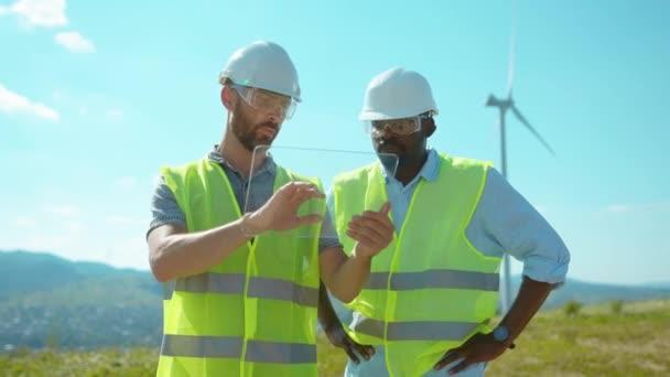 Dva inženýři držet sklo futuistic gadget tablet počítačový hologram ve speciální uniformě stojan diskutovat poblíž větrných mlýnů v polích týmová práce spolupráce mluvit zblízka zpomalit film