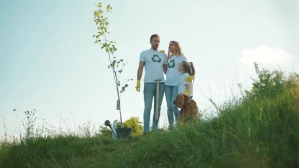 Shot of happy family with dog plant tree stand hug each other care green garden man environment agriculture planet ecology teamwork gardening slow motion