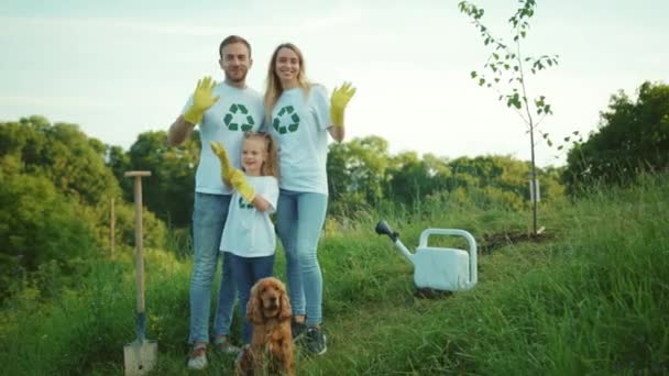 Young family with dog plant tree stand look at camera waving his hand hug each other care green garden man environment agriculture planet ecology teamwork gardening slow motion