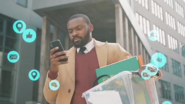 NEW YORK - Březen, 28, 2020: Africký Američan používá telefonní stojan s box osobní věci vypálené psaní mediální ikony modrá animace hlasitá technologie internet síťování virtuální rozhraní coronavirus