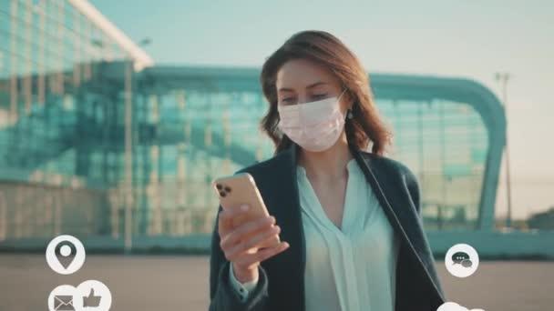 NEW YORK - Březen, 28, 2020: Mladá žena nosí ochranné masky používat telefon chůze v blízkosti letiště COVID-19 coronavirus infekce pandemie sociální média ikony bílá animace hlasité technologie internet