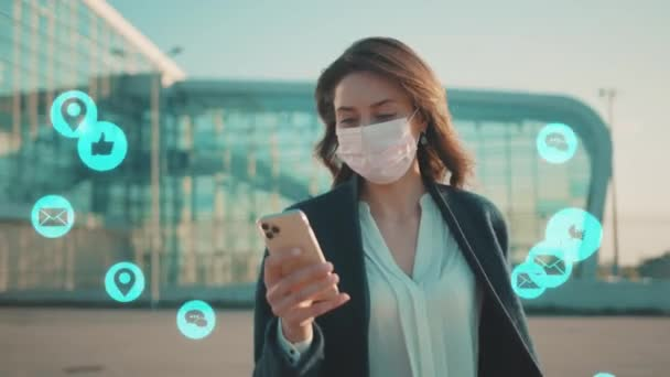 NEW YORK - March, 28, 2020: Woman wearing Protective Face Mask use phone walking near airport COVID-19 coronavirus infection pandemic social media icons blue animation loud technology internet
