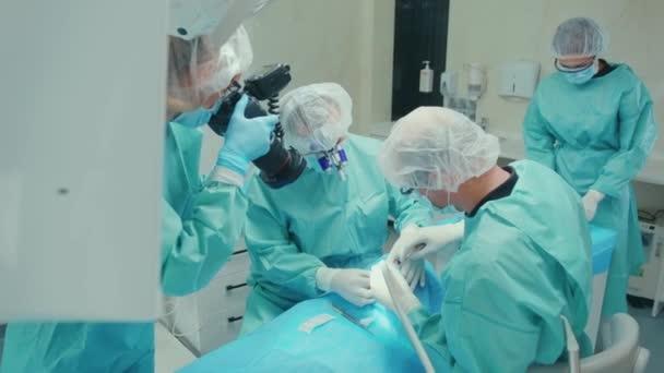 Teamwork Zahnarzt tragen Schutzanzug und Handschuhe arbeiten an Patienten zahnchirurgische Operation mit Unterstützung Spezialisten medizinische Infektionshygiene Zeitlupe