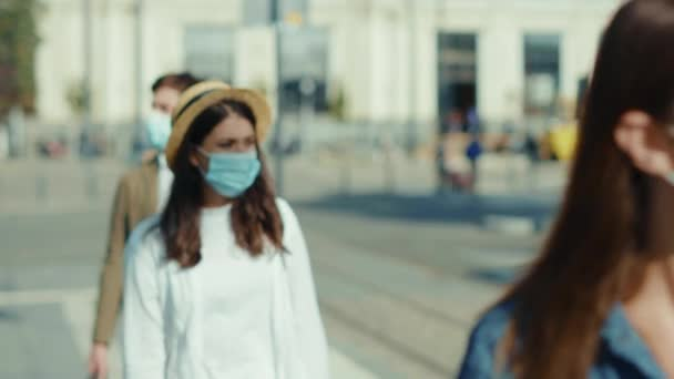 Junge Männer und Frauen in medizinischer Maske stehen Schlange an einer Bushaltestelle und halten sicheren sozialen Abstand auf der Straße.
