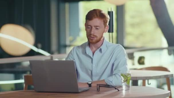 Rothaariger selbstbewusster Geschäftsmann, der eine Online-Rede vor der Webcam hält und per Laptop-Videokonferenz-Webinar mit dem Personalmanager verhandelt.