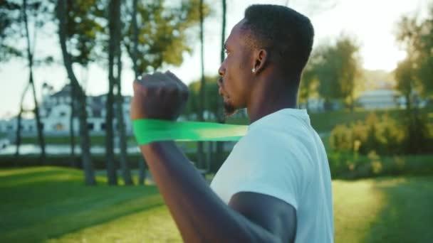 Dobře vycvičený černý sportovec dělá fyzické strečink cvičení na pažích pomocí elastických pásů odporu v krásné zelené krajině na slunné časné ráno.