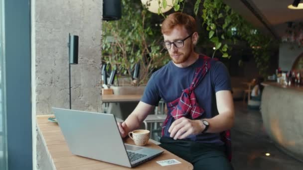 Smart ginger office executive business manager recruiter working on laptop computer drinking coffee having lunch in modern restaurant. Coworking space. Businessman.