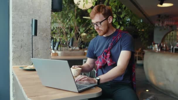 Ginger entrepreneur working on coffee break in the cafe drinking espresso. Handsome stylish businessman freelancer doing distant project on laptop computer.