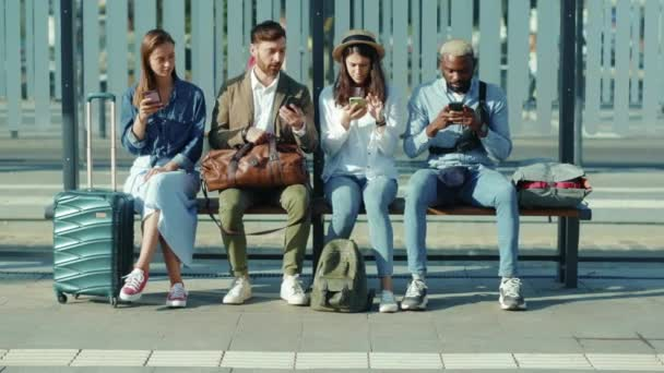 On bus stop multiethnic young travellers men and women sitting on bench talking use phone together street stylish summer sunny tourists outdoors slow motion