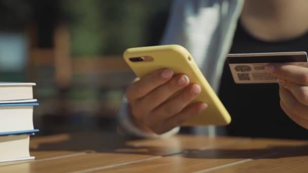 ÚJ YORK - Június 15, 2019: Ügyfél fizet a rendelés a kávézóban fizetési terminál segítségével NFC okostelefon technológia. Egy közeli lány mobiltelefont használ a bankautomatán..