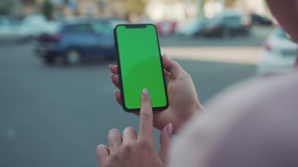 NEW YORK - 5. April 2018: Hände junge Frau halten und berühren Telefon mit grünem Bildschirm vertikal in der Straße Internet-Technologie Touch Business-Nachricht mobile Smart-Text-Vernetzung im Freien langsam
