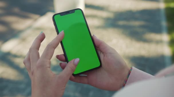 NEW YORK - 5. dubna 2018: Close up of woman hands holding and touch phone with green screen vertiktically in the street internet technology touch business message mobile smart text networking outdoors