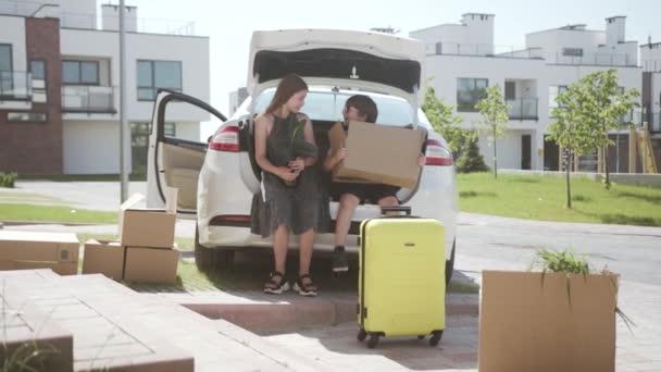 Dva šťastní dětští sourozenci spolu mluví v kufru auta a nakládají zboží. Krásný portrét bratra a sestry. Mladá rodina cestuje autem v létě.