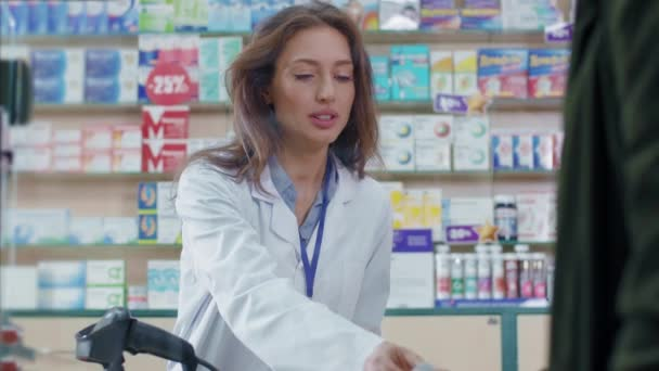 Caucasian beautiful young smart woman pharmacist selling drugs and giving consultatation to male patient. Modern drugstore. Medication and healthcare. Close-up.