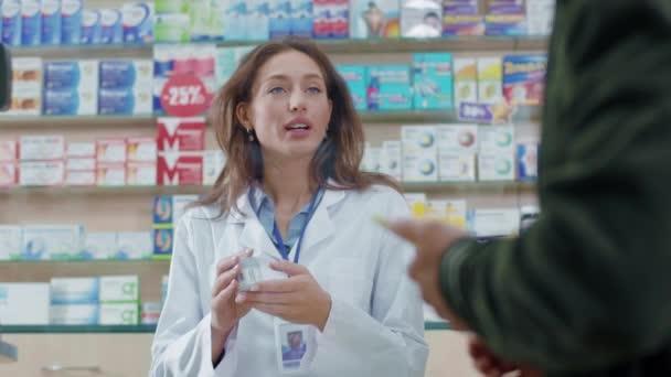NEW YORK - 5. Oktober 2020: Apothekerin gibt männlichen Patienten in der Apotheke verschriebene Medikamente. Junge Beraterin tippt Preis auf Kreditkartenautomat.