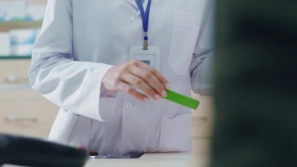 Handschuss einer Pharmazeutin, die den Preis der Medikamentenverpackung überprüft, mit der Medikamente an den Kunden verkauft werden. Männlicher Patient bereitet Kreditkarte für die Zahlung vor. Medikationskonzept.