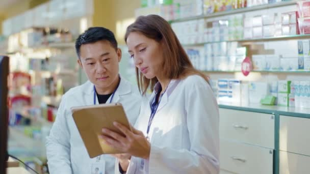 Asian adult and younger female intern cooperating in drugstore. Aspiring woman apothecarist asking advice from male colleague learning drugs in pharmacy using tablet.