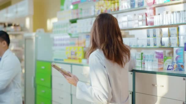 Pharmacy female consultant using digital tablet for learning drugs searching medication details online coworking in professional drugstore. People and occupation. Medical sector.