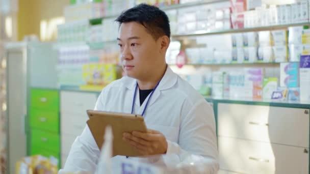 Asiatische erwachsene Apotheker suchen Medikamenteninformationen medizinische Rezept mit Computer-Tablet in der Apotheke. Drogerie. Berufstätige.