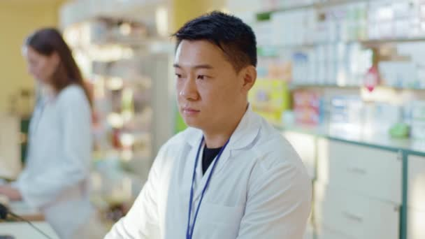 Chinese medical pharmacist browsing computer internet database examining drugs and coworking with woman. Portrait of serious professional asian druggist. Drugstore.