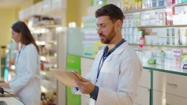 Male caucasian pharmacy intern exploring medications with digital tablet asking advice from professional apothecarist cooperating in drugstore. Healthcare and medicine.
