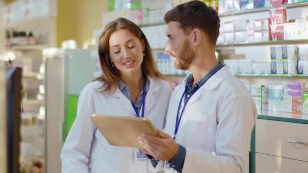 Couple of male and female apothecarists discussing medications sharing communicating using tablet computer for management. Pharmacists. Coworkers. Medicare concept.