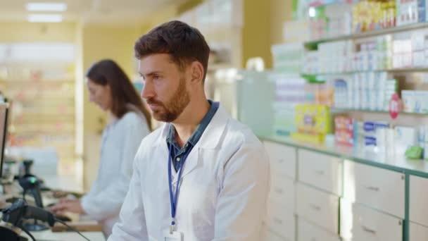 Der bärtige erwachsene Apotheker sucht in der Drogerie am Computer nach Medikamenten und blickt dann in die Kamera. Facharzt. Medizinisches Personal. Apotheke.