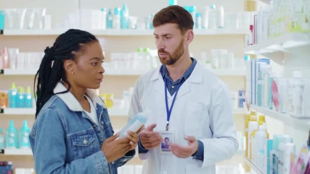 African american woman consulting with pharmacist male, discussing healthcare medication and inspecting beauty face body skincare products in drugstore.