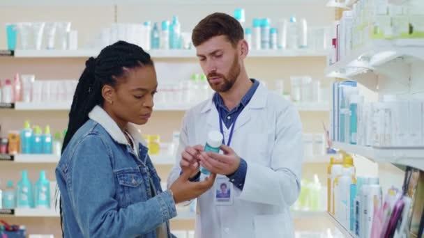 NEW YORK - 5. Oktober 2020: Apotheracist berät Frauen bei medizinischen Behandlungen in der Drogerie. Afrikanische amerikanische Patientin Mädchen wählt Hautpflege Kosmetik Medikament. Apothekenkonzept.