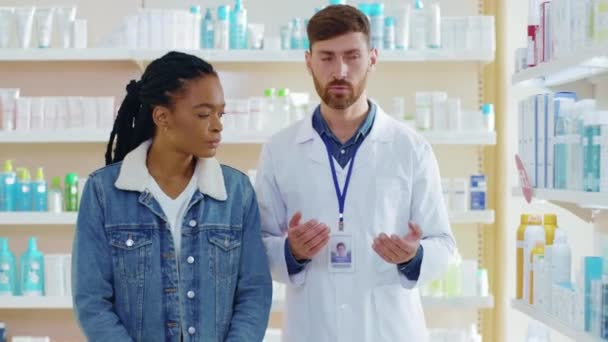 Healthcare specialist worker consulting afro-american woman patient showing healthy beauty face care treatment products in pharmacy store. Health care. Drugstore.