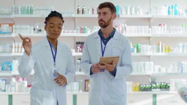 African american female pharmacist consults male intern using tablet computer examining medications and drugs in pharmacy healthcare center. Collaboration. Mixed race.