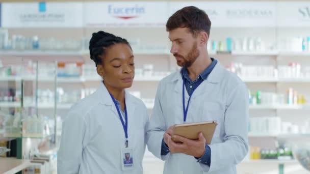 NEW YORK - 5. Oktober 2020: Schwarze Ärztin und bärtige männliche Praktikantin diskutieren über verschriebene Medikamente zur Behandlung von Patienten. Verschiedene medizinische Experten verschiedener Rassen. Apotheke. Drogerie.