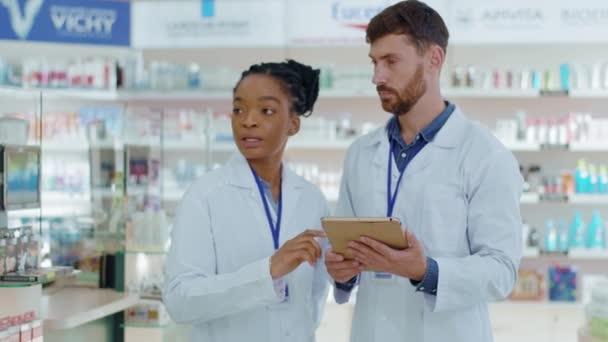 NEW YORK - 5. Oktober 2020: Apothekenkonzept. Zwei Medizinpharmazeuten lernen Medikamentengebrauch und Medikamentenrezepte und notieren digitale Tablet-Touchscreens. Drogeriemarkt-Angestellte. Zusammenarbeit.