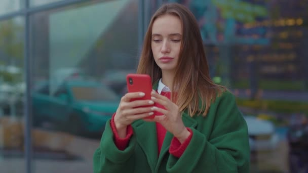 Dissatisfied young woman uses phone in the city center on Christmas time internet mobile adult caucasian cellphone street urban winter young attractive beautiful cell slow motion