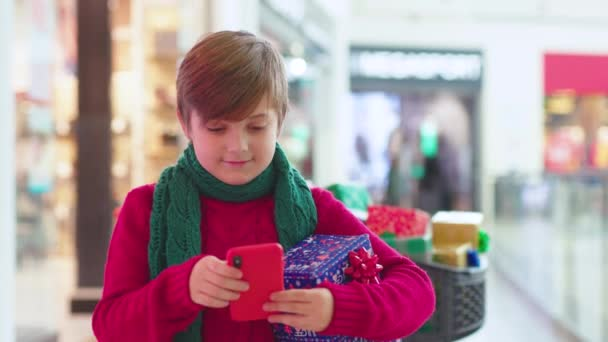 Chlapec stojí v nákupním středisku s vánoční dárek krabice použít telefon dítě rodina atraktivní teenager děti veselé štěstí dovolená dítě usmívá dětství zpomalený film