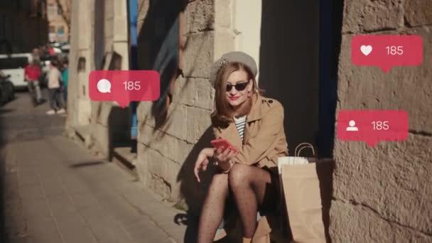 Stylová mladá žena s červenou rtěnkou nosí klobouk kabát sedí v kavárně snídaně použít telefon sociální média ikony jako komentář následovník počítadlo rychlé zvýšení vlivnější blog portrét venku zpomalený pohyb