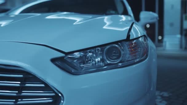 Close-up details of anonymous tuning luxury car with headlights switched on. Modern white car front right light flashing at camera on parking space. Car details.