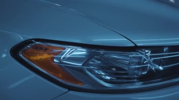 Close-up of details of headlights of white tuning prestigious modern car parked outdoor in open space. Night time. Car dealerships, driving cars, luxury cars concept.