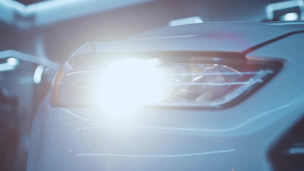 Attractive white modern car standing at parking space flashing with turned on bright headlights slow motion in close-up. Car dealership and luxury cars concept.